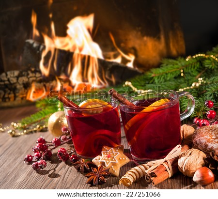 Two glasses of  mulled wine with christmas decoration at romantic fireplace - stock photo