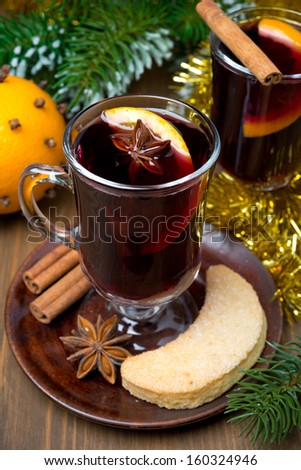 two glasses of mulled wine with spices in glass and cookies, vertical - stock photo