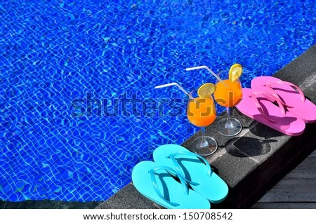 Two glasses of orange juice and colored sandals by the swimming pool -- Vacation Concept  - stock photo
