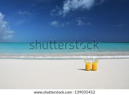 Two glasses of orange juice on the sandy beach - stock photo