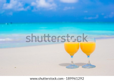 Two glasses of orange juice on tropical white beach