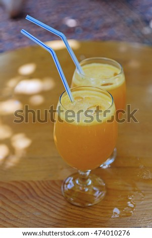 Two glasses of orange juice with plastic straw on wooden table