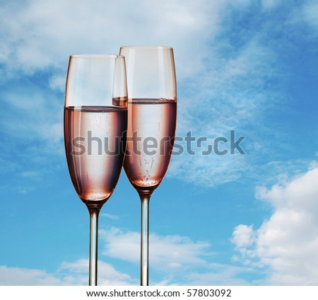 Two glasses of pink champagne on blue sky - stock photo