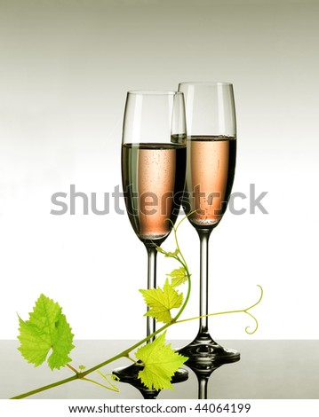Two glasses of pink champagne with fresh grapevine sprig - stock photo
