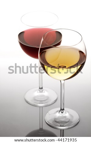 Two glasses of red and white wine in back light on light background. - stock photo