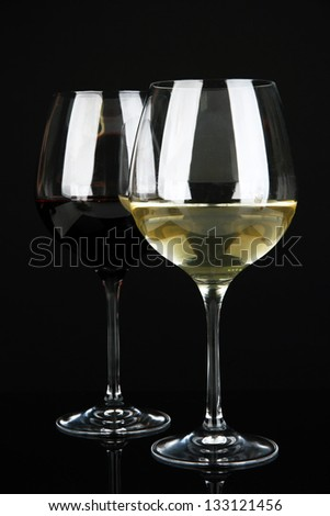 Two glasses of  red and white wine, isolated on black - stock photo