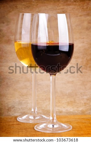 two glasses of red and white wine on a wooden background