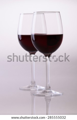 Two glasses of red dessert wine standing on grey white backdrop, vertical picture - stock photo