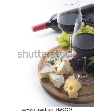 Two glasses of red wine, bottle, cheese and grapes - stock photo