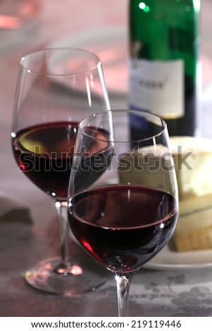 Two glasses of red wine, bottle of red wine a cheese  still life - stock photo