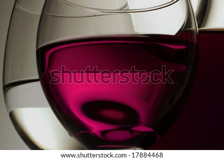 Two glasses of red wine of white wine on it is black a white background and a wine bottle on a background