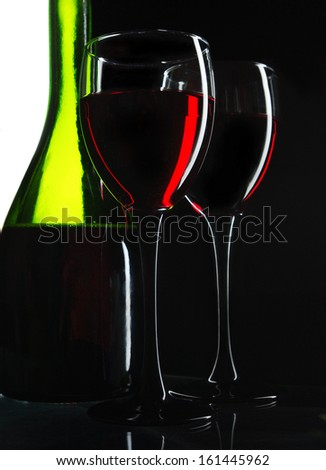 Two glasses of red wine, one bottle. Close up. Black background