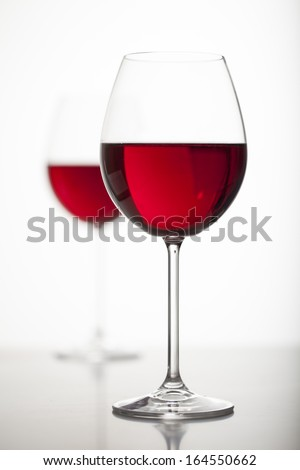 Two glasses of red wine over white background - stock photo
