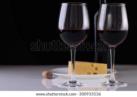 Two glasses of red wine standing with bottle and fresh tasty cheese on plate and cork on white table top on black studio background copyspace, horizontal picture - stock photo