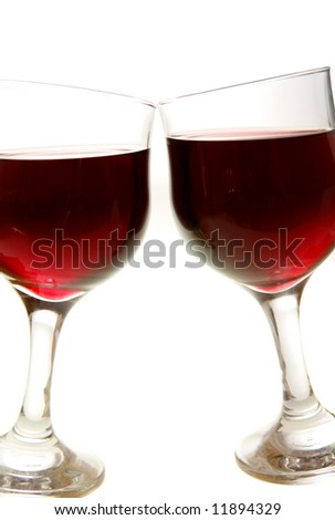 Two glasses of red wine touched together as if in a toast.