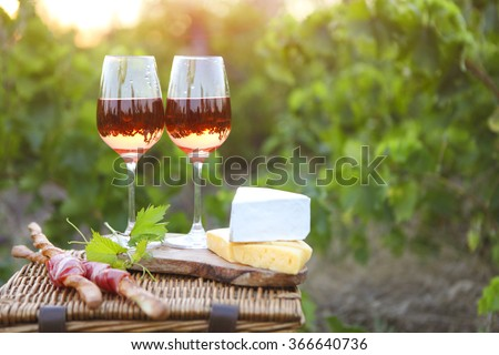 Two glasses of rose wine with bread, meat, grape and cheese on the vineyard background - stock photo