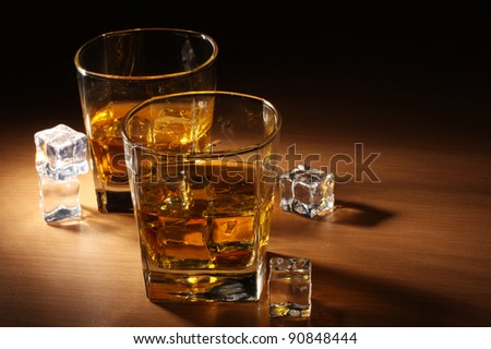 two glasses of scotch whiskey and ice on wooden table - stock photo
