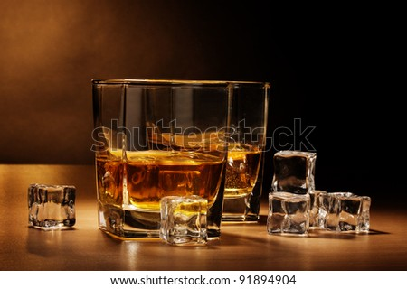 two glasses of scotch whiskey and ice on wooden table on brown background - stock photo