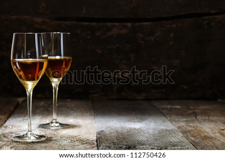 Two glasses of sherry on brown wooden background with copyspace - stock photo