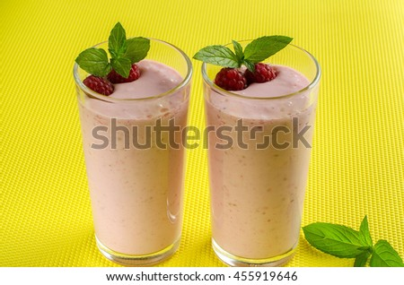 Two glasses of smoothie. Raspberry smoothies. Yogurt with berries. Mint leaves. Fresh raspberries.  Yellow background.