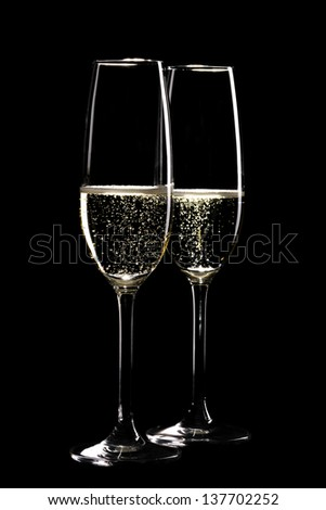 Two glasses of sparkling champagne in front of black background