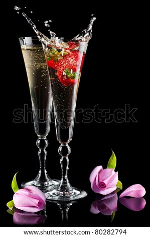 Two glasses of sparkling splashing wine (champagne) with pink roses and strawberry on black - stock photo