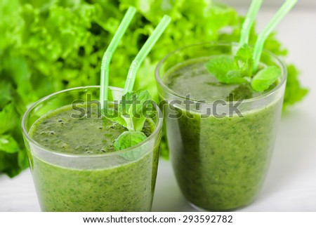 Two glasses of tasty healthy natural green smoothies made with fresh lettuce, mint, dill, parsley and a banana on a white wooden table. Healthy food, breakfast vegetarian raw food. - stock photo