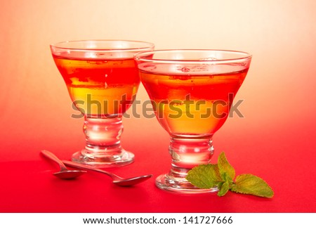 Two glasses of the fruit jelly, two teaspoons, spearmint leaf on a pink background