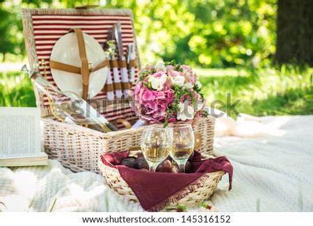 Two glasses of the white wine with picnic basket. - stock photo