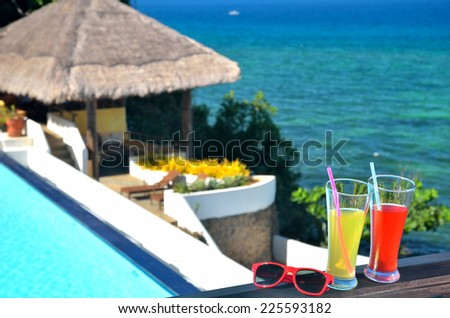 Two glasses of tropical fruit juice and sunglasses beside blue pool with seascape view - stock photo