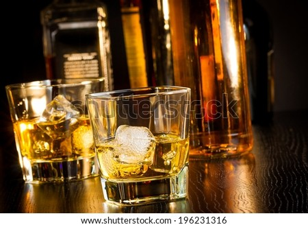 two glasses of whiskey in front of bottles on wood table - stock photo