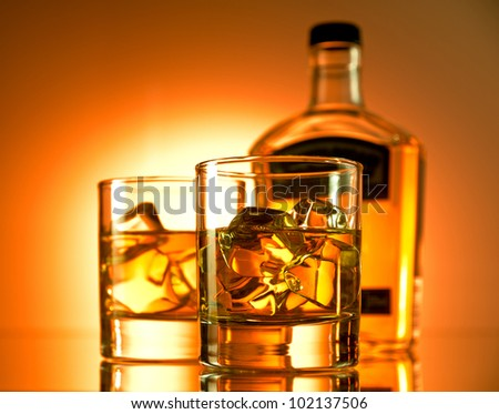 Two glasses of whiskey with a bottle in the background - stock photo