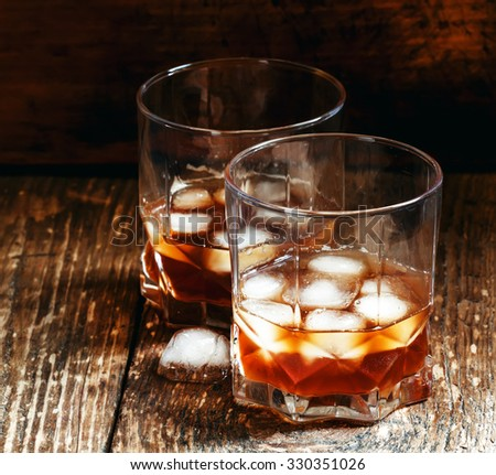 Two glasses of whiskey with ice, dark toned image, selective focus