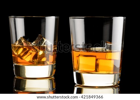 Two glasses of whiskey with ice on black background. Whisky on rocks - stock photo