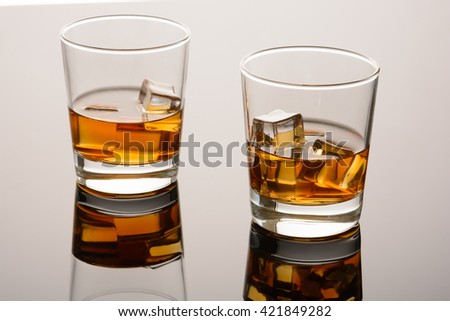 Two glasses of whiskey with ice on mirror surface. Whisky on rocks - stock photo