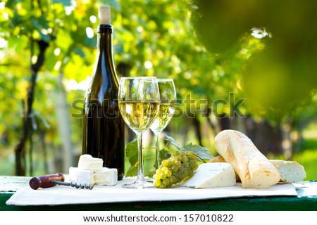 Two glasses of white wine, bottle, cheese and baguette - stock photo