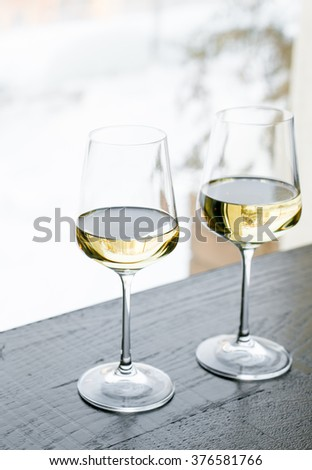 Two glasses of white wine on a table, winter day on a background