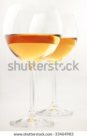 Two glasses of white wine on light background. - stock photo