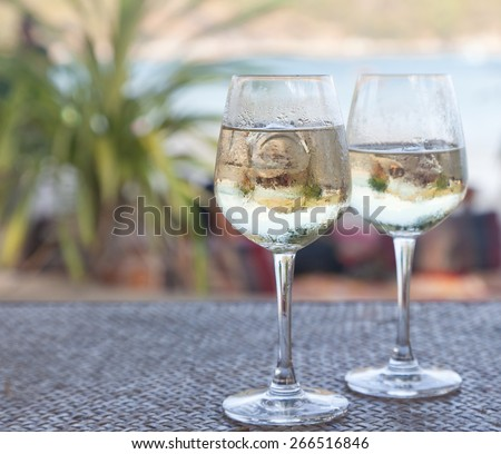 two glasses of white wine with ice on a table at the beach cafe - stock photo