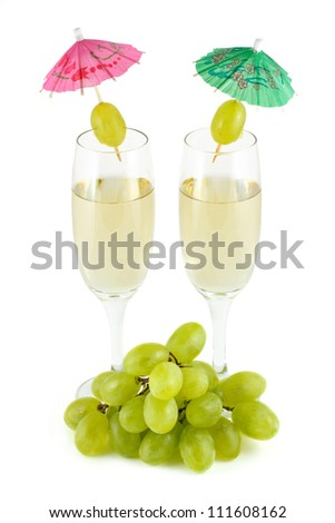 two glasses of wine and a bunch of grapes. Cocktail umbrellas isolated on a white background - stock photo