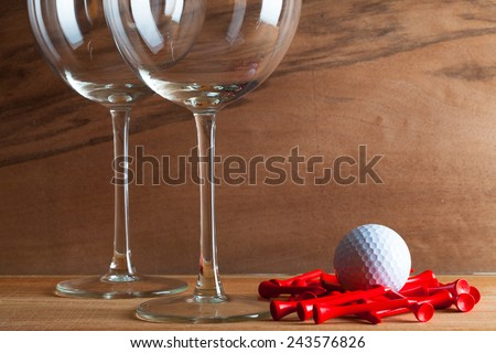 Two glasses  of wine and golf equipments on the wooden background from real wood veneer with interesting growth - stock photo