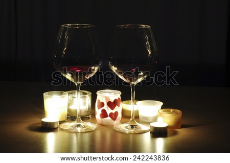 Two glasses of wine, by candle light, with a romantic theme - stock photo