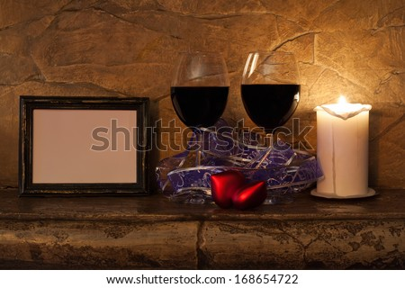 Two glasses of wine, candle and teddy red heart on stone wall background. Valentines day. Romantic still-life.  - stock photo