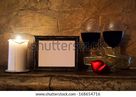 Two glasses of wine, candle, teddy red heart and vintage photo frame on stone wall background. Valentines day. Romantic still-life.  - stock photo