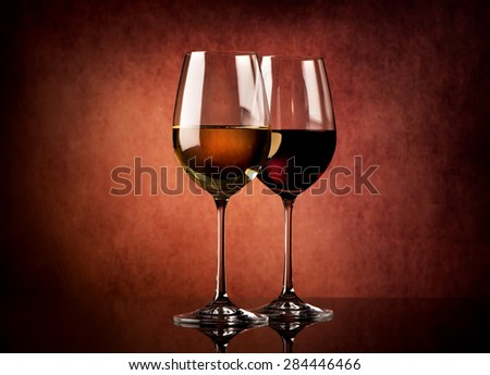 Two glasses of wine on a textured background - stock photo