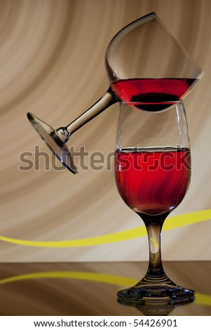 Two glasses of wine, one balanced on the other, with brown background - stock photo