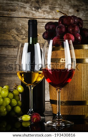two glasses of wine with fresh grapes, bottle and barrel in front of old grunge wooden planks - stock photo