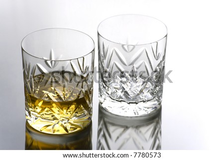 Two Glasses , one full of Whisky on a Reflective Surface with Copy Space - stock photo
