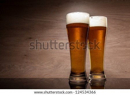 Two glasses with beer served on the table. - stock photo