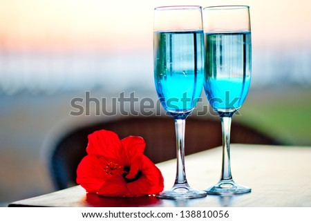 Two glasses with blue alcohol cocktail with an exotic flower on the table - stock photo